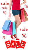 Concept of discount. Female in red shoes holding shopping bags isolated on white — Stock Photo
