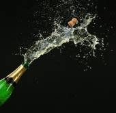 Bottle of champagne with splashes on black background — Stock Photo