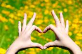Young girl holding hands in heart shape framing on yellow flowers background — Stock Photo