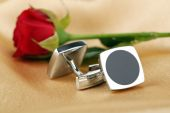 Pair of cuff links with red rose on light silk fabric background — Stock Photo
