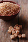 Brown sugar cubes and crystal sugar in bowl on wooden background — Stockfoto
