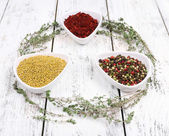 Spices in glass round bowls with herbs on wooden background — Photo