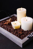 Candles on vintage tray with coffee grains and spices on wooden table, on dark background — Stockfoto