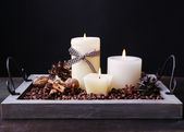Candles on vintage tray with coffee grains and spices, bumps on wooden table, on dark background — Foto Stock