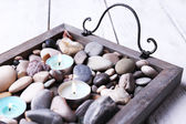 Candles on vintage tray with sea pebbles, on wooden background — Stock Photo