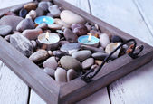 Candles on vintage tray with sea pebbles, on wooden background — Foto Stock