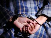 Criminal hands locked in handcuffs on dark background — Stock Photo