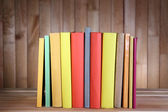 Books on wooden table on wooden wall background — Stock Photo
