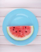 Water melon on blue plate on wooden background — Stock Photo