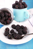 Sweet blackberries in mugs and on plate, on color wooden background — Stock Photo