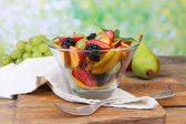 Fresh tasty fruit salad on wooden table, on nature background — Stock Photo