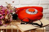 Retro phone and glasses on table in room — Foto Stock