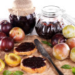 Plum jam, slices of bread with plum jam and fresh plums in glass dish on piece of paper on wooden table on light background — Stock Photo #52340079