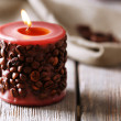 Candle decorated with coffee beans on wooden table, close up — Stock Photo #52341441