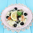 Fresh prawns with olives, lemon and parsley in white sauce on pink round plate on a lace napkin on blue wooden background — Stock Photo #52348839