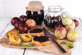 Plum jam, slices of bread with plum jam and fresh plums in glass dish on piece of paper on wooden table on light background — Stock Photo