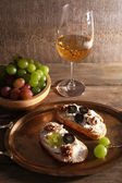 Beautiful still life with wine, cheese and ripe grape on wooden background — Stock Photo