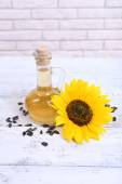 Sunflower with seeds and oil on table on brick wall background — Stock Photo