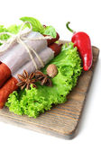 Smoked thin sausages  with lettuce salad leaves on wooden cutting board, isolated on white — Stock Photo