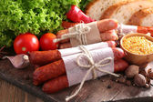 Assortment of thin sausages, bread, mustard in bowl and spices on cutting board, on wooden background — Stockfoto