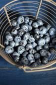 Arándanos maduros sabrosos en cesta metálica, sobre fondo de madera — Foto de Stock