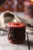 Candle decorated with coffee beans on wooden table, close up — Stockfoto