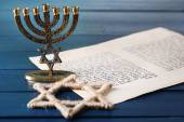 Menorah, star of David and page of Genesis book on wooden background — Stock Photo