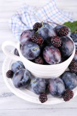 Ripe sweet plums in big cup, on grey wooden table — Stock Photo