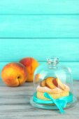 Tasty mini cake with fresh peach on glass saucer with lid, on wooden table — Stock Photo