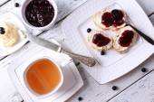 Fresh toasts with homemade butter and blackcurrant jam on wooden background — Foto Stock