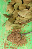 Bay leaves and seeds on green wooden background — Stock Photo
