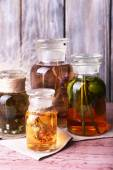 Bottles of herbal tincture on a napkin on  wooden table in front of wooden wall — Stock Photo