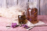 Bottles of herbal tincture and brunch of flowers on a napkin on a wooden table in front of wooden wall — Stock Photo