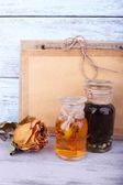 Bottles of herbal tincture, book and dried rose on wooden background  — Stock Photo