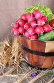 Big round wooden basket with vegetables on sacking background — Stock Photo