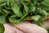 Tuft of fresh sorrel in wooden plate on piece of sacking on wooden background — Stock Photo