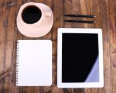 Tablet, cup of coffee, notebook and pens on wooden background — Stock Photo
