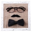 Glasses, mustache and bow tie forming man face on color board, isolated on white — Stock Photo #52350205