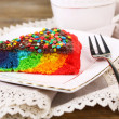 Delicious rainbow cake on plate and cup with hot drink, on wooden background — Stock Photo #52350919