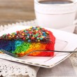 Delicious rainbow cake on plate and cup with hot drink, on wooden background — Stock Photo #52350927
