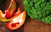 Green fresh parsley and sliced bell pepper  on wooden background — Stock Photo