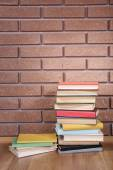 Books on wooden table on brick wall background — Stockfoto