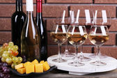 Bottles and glasses of wine, cheese and ripe grapes on box on brick wall background — Stock Photo