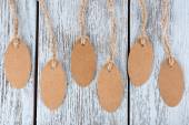Brown tags on wooden background — Stock Photo