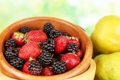 Berries in bowl with pears on table on bright background — Foto de Stock