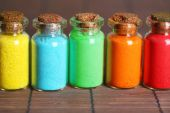 Bottles with colorful dry pigments on bamboo mat background — Stock Photo