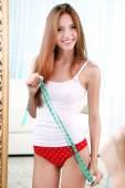 Beautiful woman with measuring tape posing near mirror in room — Stock Photo