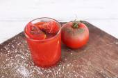 Glass of tomato juice with spices and fresh tomatoes on wooden table — Stock fotografie