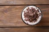 Yogurt, with chocolate cream, chopped chocolate and muesli served in glass on wooden background — Stockfoto