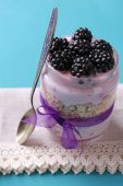 Healthy breakfast - yogurt with  blackberries and muesli served in glass jar, on color wooden background  — Stock Photo